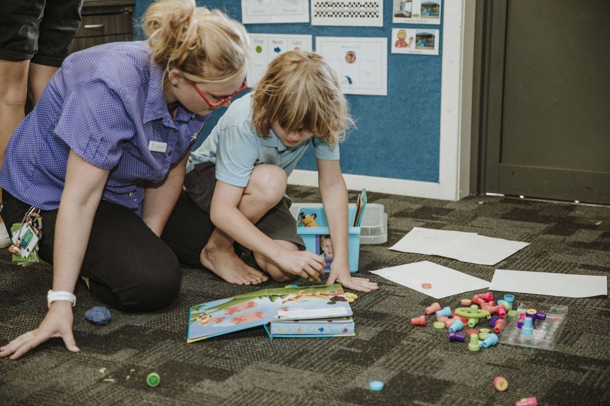 A teacher helps a student with a puzzle on the classroom floor at Aspect Hunter School