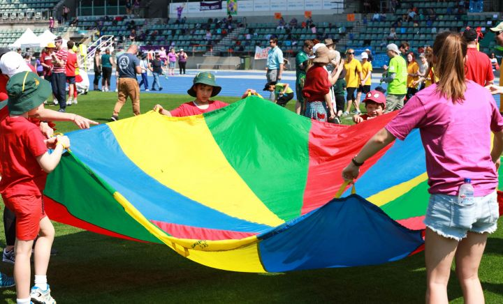 Students and adult play the parachute game in the stadium at Sports Carnival 2018