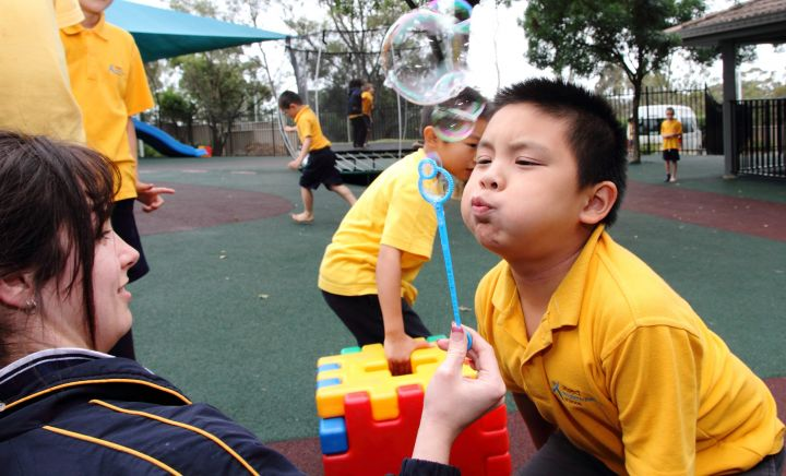 A student blows bubbles with a teacher within the playground at Western Sydney School