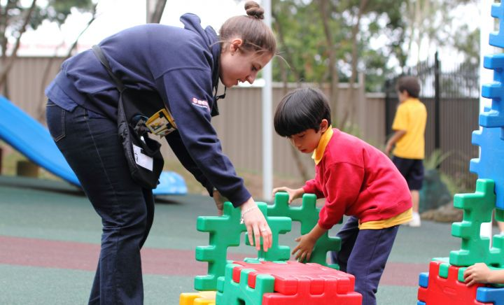 A teacher and student interact within the playground at Western Sydney School