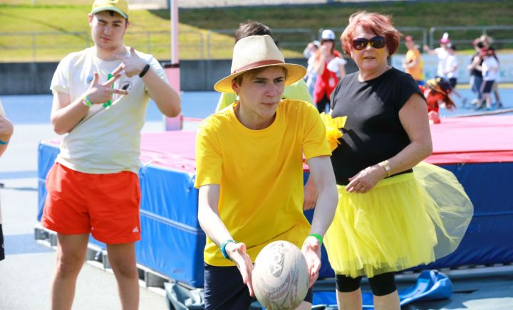Students and adult play with a rugby ball at Sports Carnival 2018